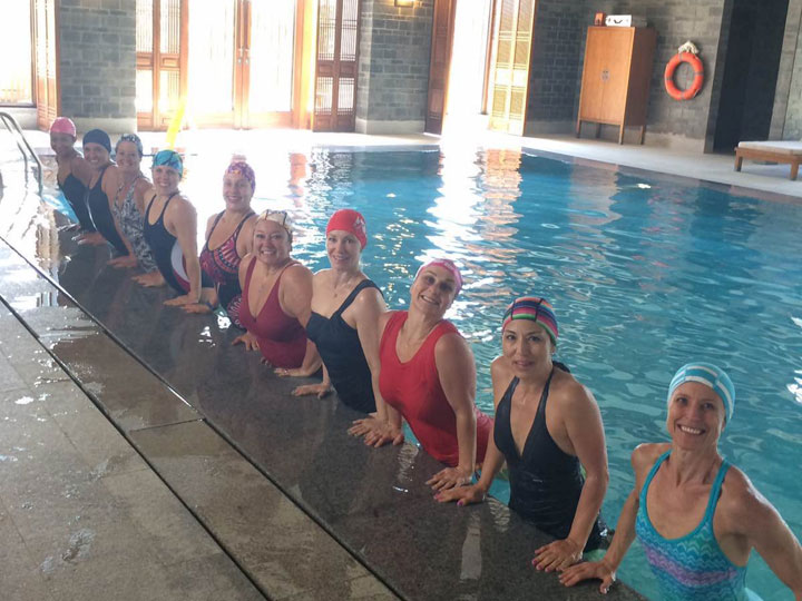 women in swim caps in pool